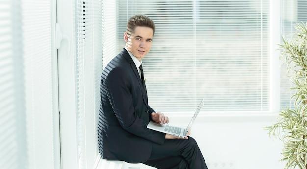 Jonge werknemer die op een laptop werkt die in de gang van het kantoor zit