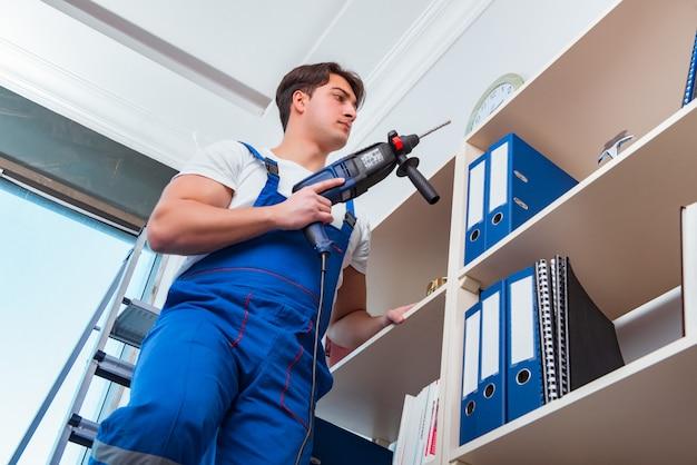 Jonge werknemer die planken in bureau herstelt