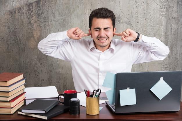 Jonge werknemer die zijn ogen en oren bij het bureau sluit.