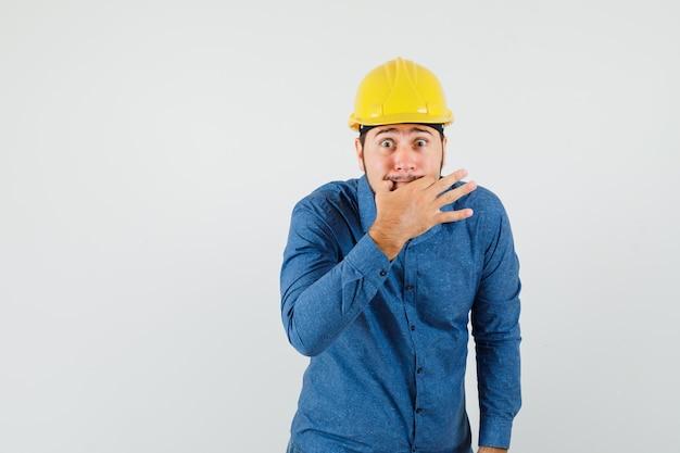 Jonge werknemer fluiten met vingers in shirt, helm en opgewonden kijken