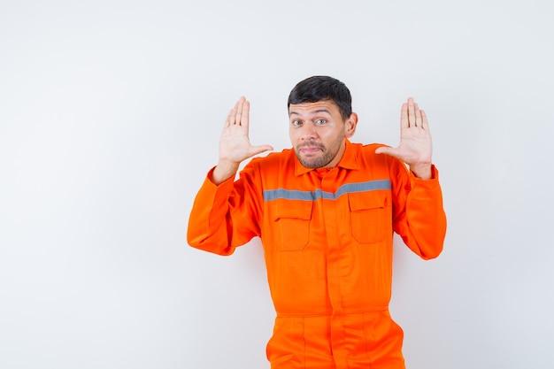 Jonge werknemer handen in overgave gebaar in uniform houden.