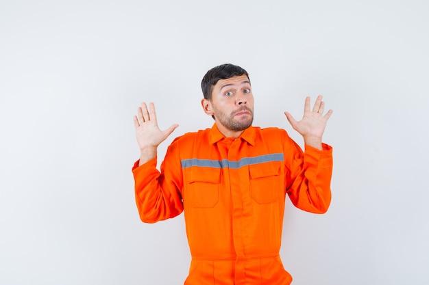 Jonge werknemer houdt handen in overgave gebaar in uniform en kijkt bang.