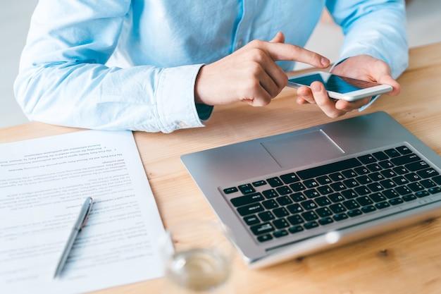 Jonge werknemer in blauw shirt zit door houten tafel laptop en scrollen in smartphone tijdens communicatie