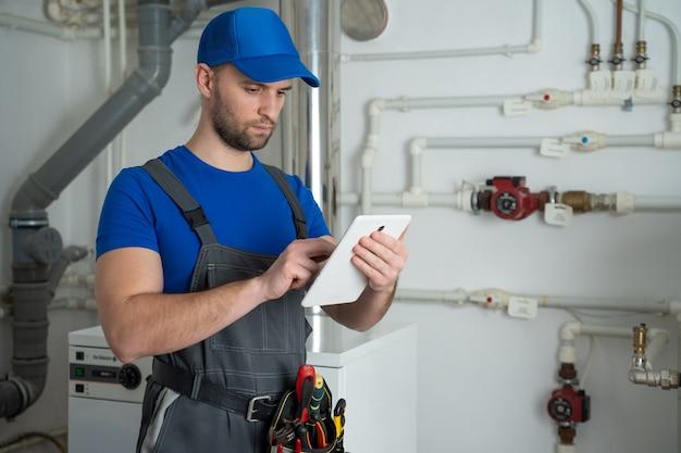 Jonge werknemer in een beschermend pak gebruikt een tablet tijdens het controleren van de ketelapparatuur in het huis