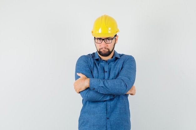 Jonge werknemer in overhemd, helm die zich met gekruiste wapens bevindt en ernstig kijkt