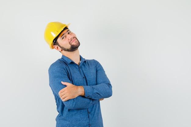 Jonge werknemer in overhemd, helm die zich met gekruiste wapens bevindt en vrolijk kijkt
