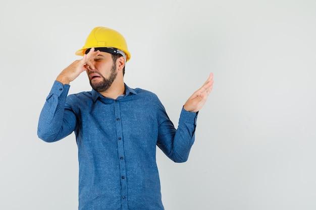 Jonge werknemer in shirt, helm knijpen neus als gevolg van stank en walgt op zoek