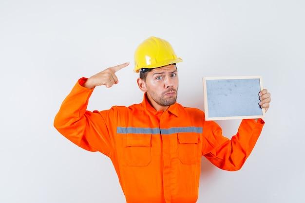 Jonge werknemer in uniform bedrijf bord, wijzend op zijn helm.