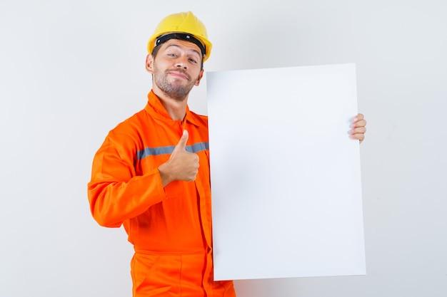 Jonge werknemer in uniform met leeg canvas, duim opdagen en vrolijk kijken.
