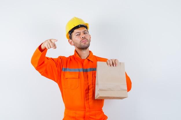 Jonge werknemer in uniform met papieren zak, wijzend op de voorkant.
