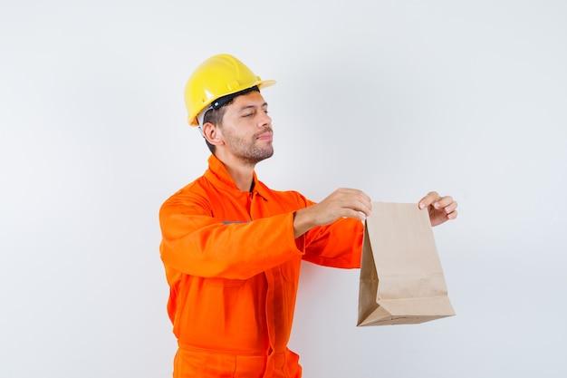 Jonge werknemer in uniform presenteert papieren zak en ziet er zachtaardig uit.