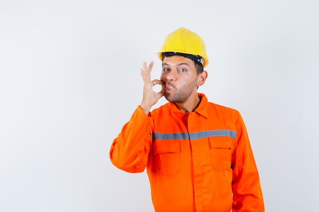 Jonge werknemer in uniform ritssluiting gebaar tonen en voorzichtig kijken.