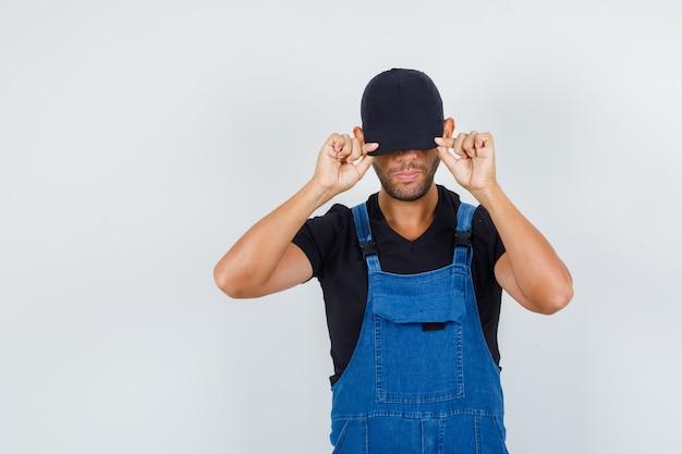 Jonge werknemer in uniform verbergt zijn gezicht achter pet en kijkt serieus, vooraanzicht.