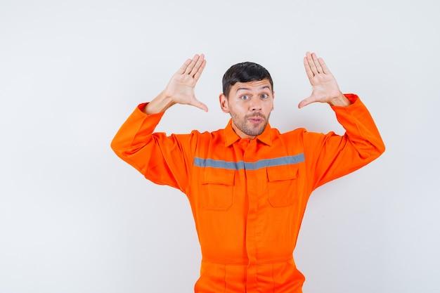 Jonge werknemer in uniform verhogen handen in overgave gebaar.