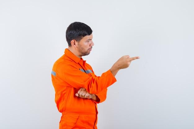 Jonge werknemer in uniform wijst naar de voorkant van hem en kijkt serieus.