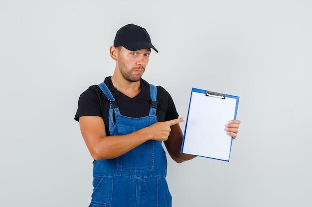 Jonge werknemer in uniform wijzend op klembord, vooraanzicht.