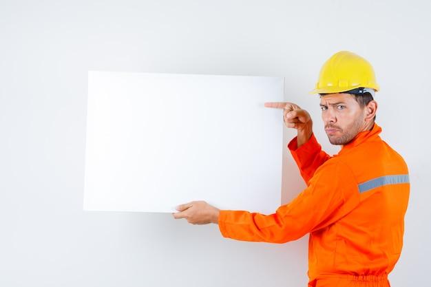 Jonge werknemer in uniform wijzend op leeg canvas en aarzelend op zoek.