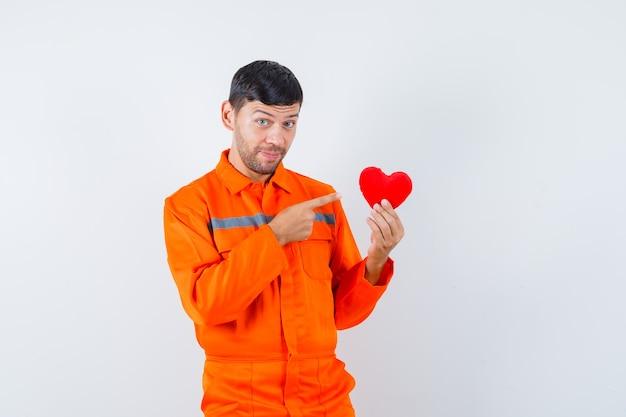 Jonge werknemer in uniform wijzend op rood hart en kijkt positief.