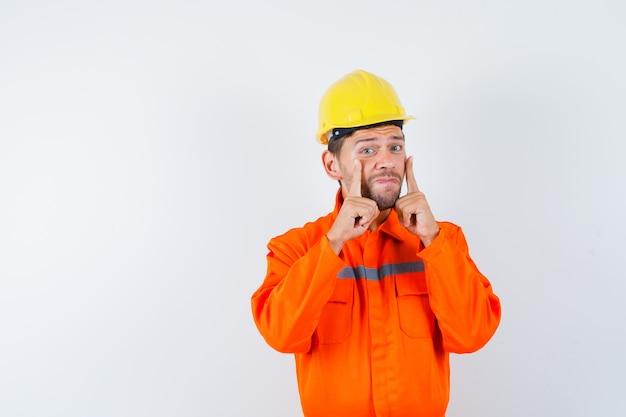 Jonge werknemer in uniform wijzend op zijn oogleden en boos kijken.