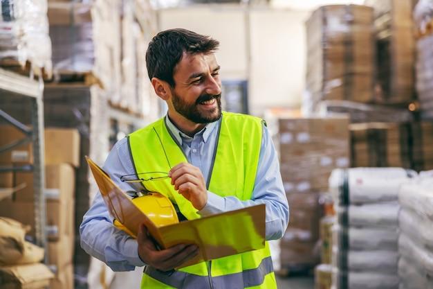 Jonge werknemer in vest en met helm onder oksel staande in magazijn en map met belangrijke documenten te houden.