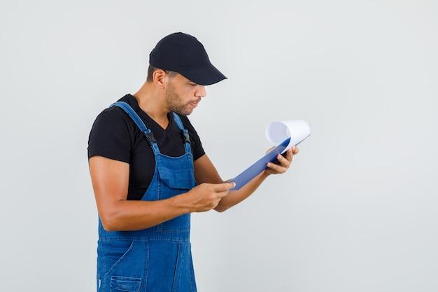 Jonge werknemer kijkt over klembord in uniform en kijkt druk, vooraanzicht.