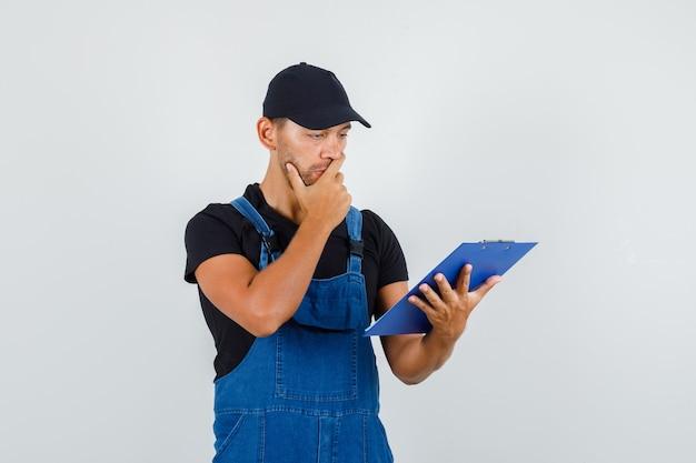 Jonge werknemer kijkt over klembord in uniform en kijkt peinzend. vooraanzicht.