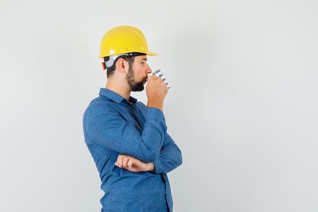 Jonge werknemer koffie drinken tijdens het denken in shirt, helm