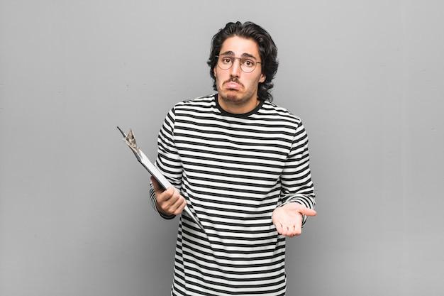Jonge werknemer man met een inventaris haalt schouders op en open ogen verward.