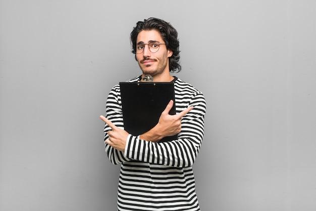 Jonge werknemer man met een inventaris opzij, probeert te kiezen tussen twee opties.