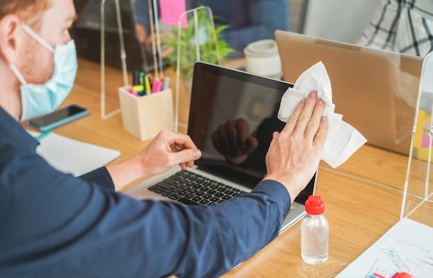 Jonge werknemer met behulp van ontsmettingsmiddel gel om zijn laptopcomputer in coworking office te desinfecteren