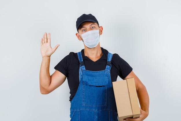 Jonge werknemer met kartonnen doos en zwaaiende hand in uniform, masker vooraanzicht.