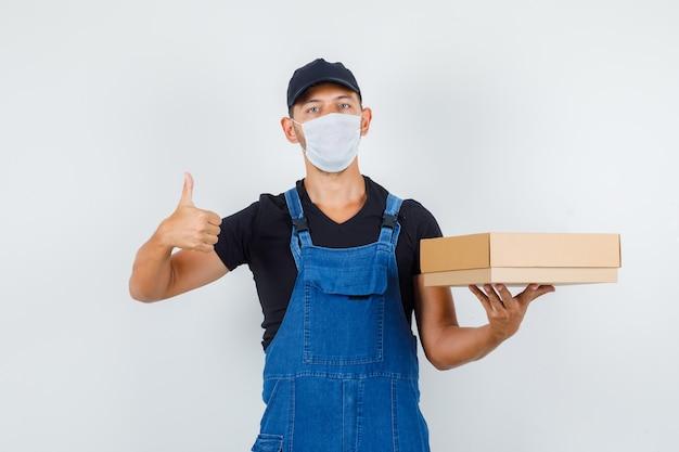 Jonge werknemer met kartonnen doos met duim omhoog in uniform, masker vooraanzicht.