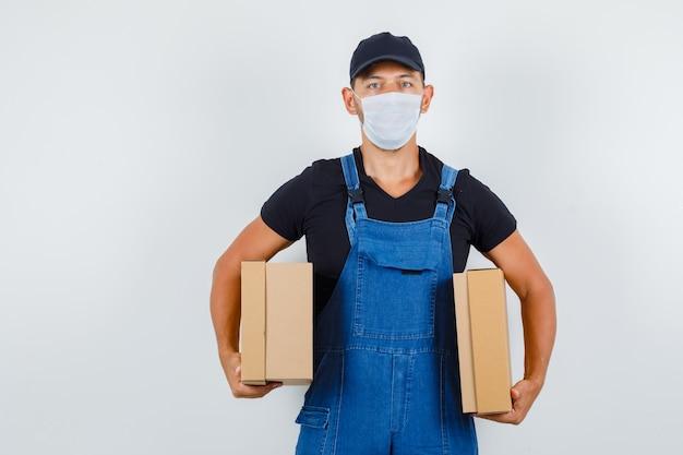 Jonge werknemer met kartonnen dozen in uniform, masker vooraanzicht.