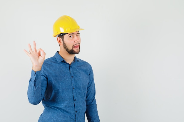 Jonge werknemer met ok gebaar, knipogend oog, tong in shirt, helm uitsteekt