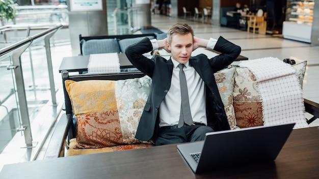 Jonge werknemer met pauze en rust na het oplossen van taak, gekleed in zwart pak in winkelcentrum