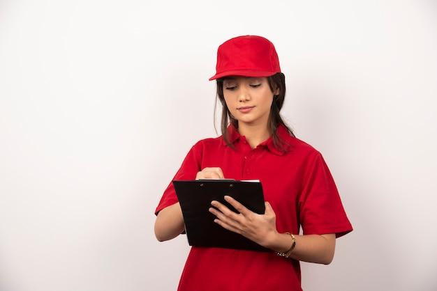 Jonge werknemer met rode uniform en klembord op witte achtergrond.
