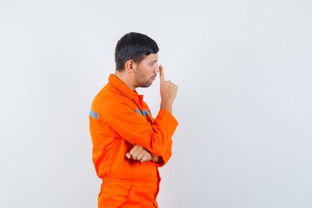 Jonge werknemer neus met vinger in uniform aan te raken en peinzend op zoek.