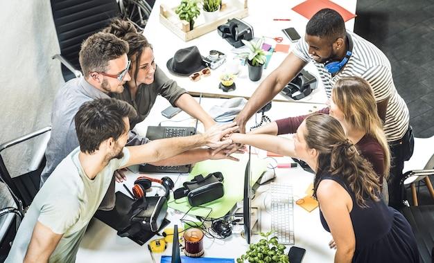 Jonge werknemer opstarten werknemers groep stapelen handen in stedelijke studio tijdens brainstormproject ondernemerschap