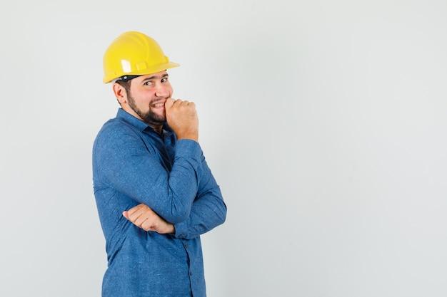 Jonge werknemer permanent in denken poseren in shirt, helm en beschaamd kijken