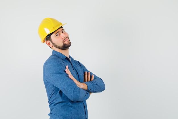 Jonge werknemer permanent met gekruiste armen in shirt, helm en op zoek zelfverzekerd.