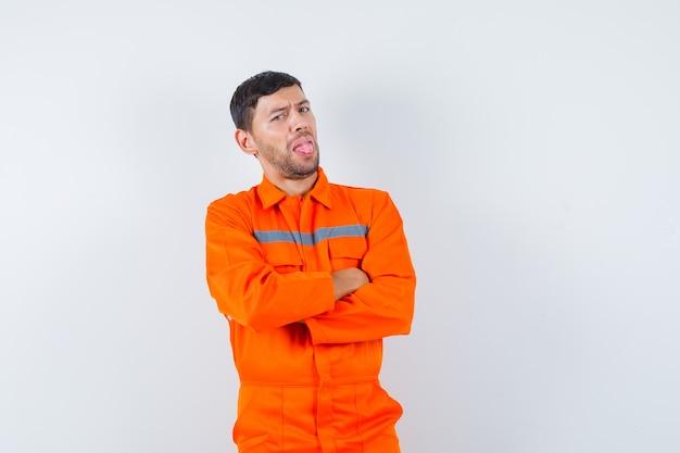 Jonge werknemer permanent met gekruiste armen, tong uitsteekt in uniform en op zoek naar ontevredenheid.