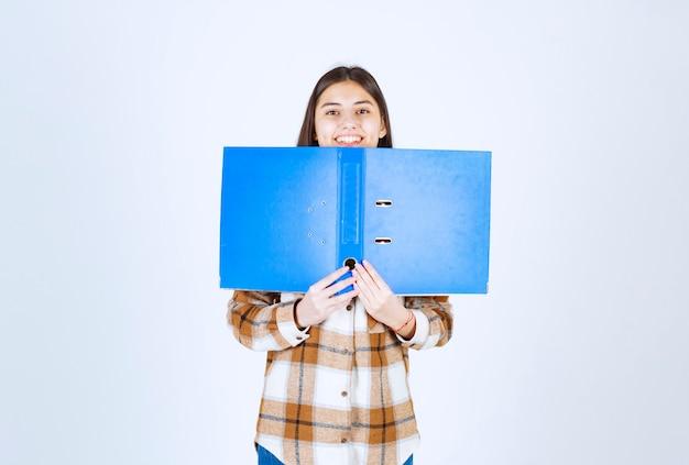 Jonge werknemer verstopt achter blauwe map op witte muur.