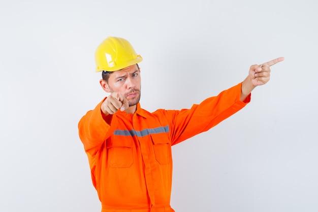Jonge werknemer wijst naar kant en weg in uniform, helm.