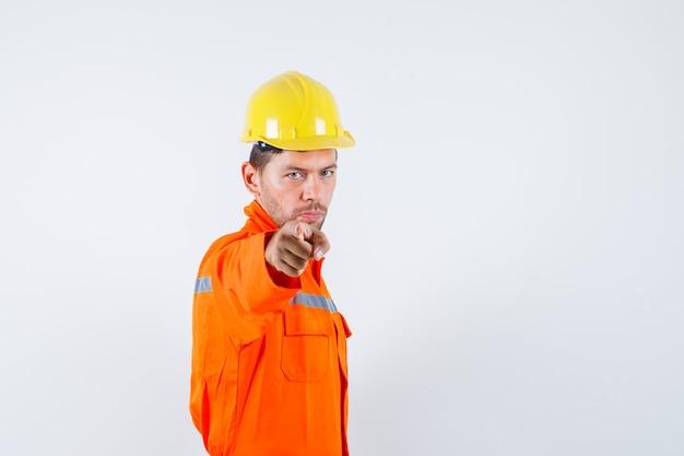 Jonge werknemer wijst naar voren in uniform, helm en kijkt serieus.