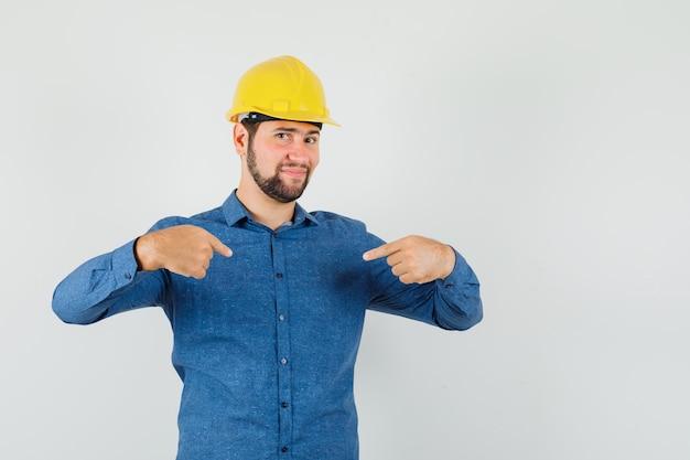 Jonge werknemer wijst naar zichzelf in shirt, helm en trots op zoek.
