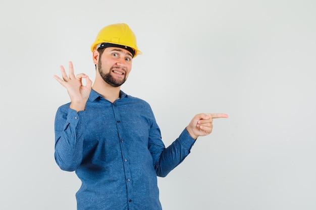 Jonge werknemer wijst opzij, toont ok teken in overhemd, helm en kijkt vrolijk