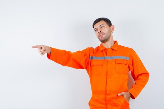 Jonge werknemer wijst weg in uniform en kijkt positief.