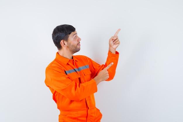 Jonge werknemer wijzend op de rechterbovenhoek in uniform en ziet er joviaal uit.