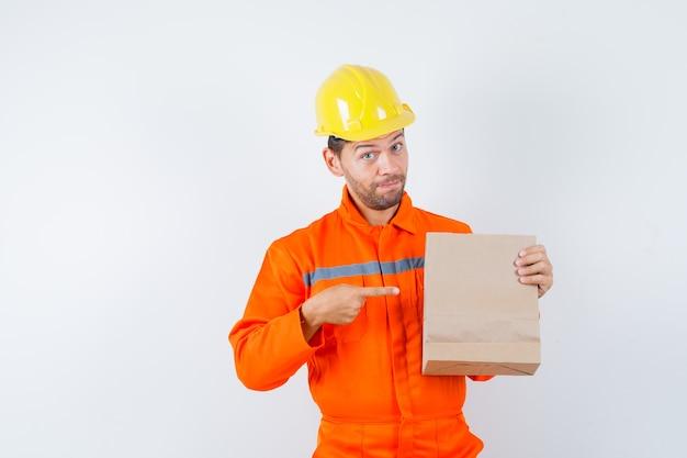 Jonge werknemer wijzend op papieren zak in uniform, helm.