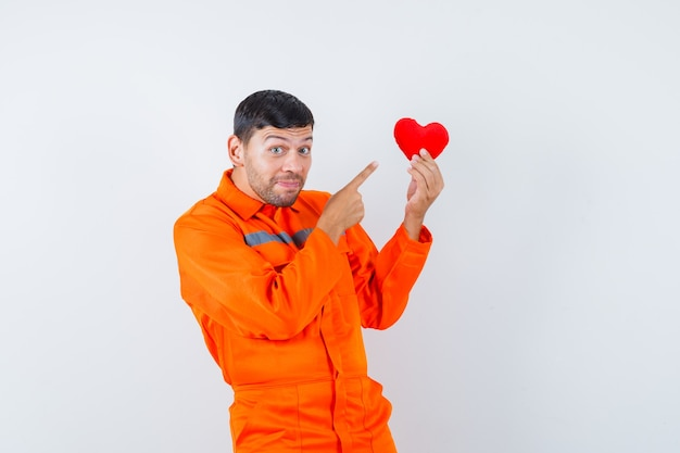 Jonge werknemer wijzend op rood hart in uniform en ziet er vrolijk uit.